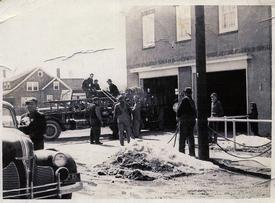 Packing hose in front of the original firehouse - Circa late 1930's