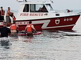 Firefighters transporting rescue equipment using a paddle board